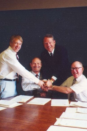 Four white men in front of paperwork doing a group handshake