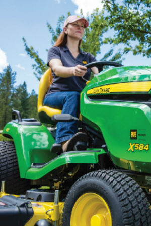 Brunette woman sitting on John Deere X584 riding lawn mower wearing work boots and pape polo shirt