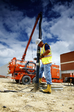 Man in work boots and safety vest stands on construction site with orange ditch witch vacuum truck